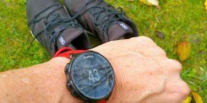 Activitytracker und Laufschuhe auf Gras